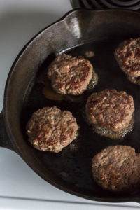 cooked slider patties in a skillet