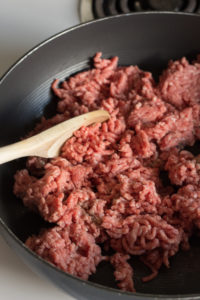 ground beef cooking in a pan with a wooden spoon