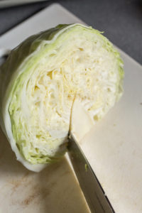 cutting the stem off half a head of green cabbage
