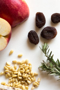 an apple, apricots, rosemary, and pine nuts on a white background