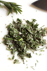 chopped rosemary on a white cutting board
