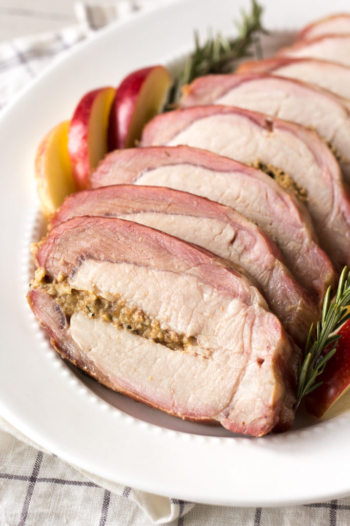 close up of sliced and smoked pork loin roast on a platter