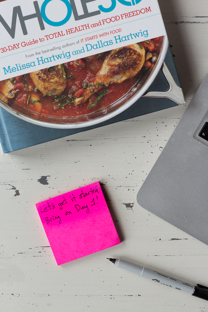 pink post it notes next to a pen, laptop, and whole30 book