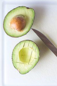 cut avocado on a cutting board with a knife