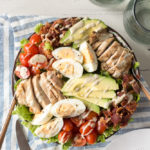 chicken cobb salad with dressing on a napkin