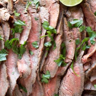 sliced of carne asada on a cutting board