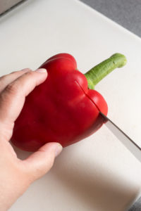 cutting into the top of a red bell pepper