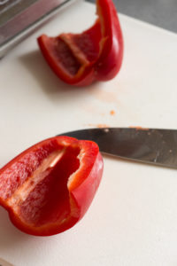 two halves of a red bell pepper on a white cutting board with a knife