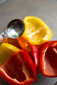 pouring oil over halved bell pepper in a bowl