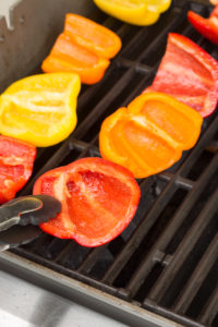a pair of tongs placing halved bell peppers on a grill