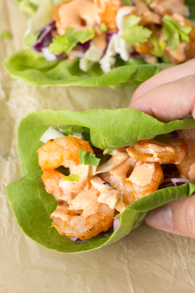 a hand grabbing a lettuce wrapped grilled shrimp taco