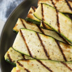 slices of grilled zucchini on a gray plate
