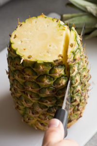 cutting the skin off the sides of a pineapple