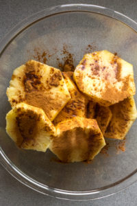 slices of pineapple in a bowl with cinnamon sprinkled on top
