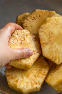 hands rubbing in oil and cinnamon onto pineapple slices