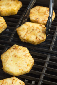 placing slices of pineapple on a grill