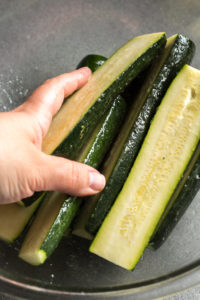 a hand spreading oil and salt over halved zucchini in a bowl