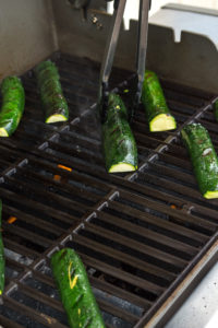 a pair of tongs flipping halved zucchini on a grill