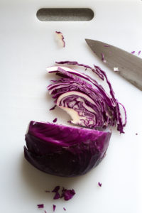 cutting purple cabbage on a white cutting board