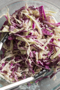 simple coleslaw in a bowl with tongs