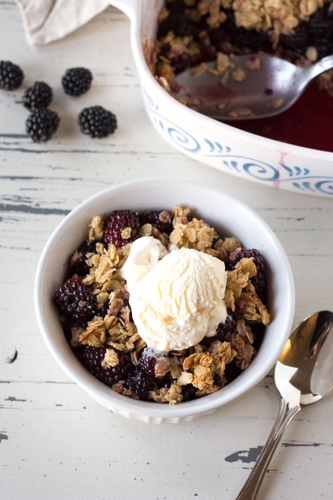 a bowl of blackberry crisp with vanilla ice cream next to a baking dish