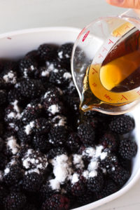 maple syrup being poured over blackberries in a baking dish
