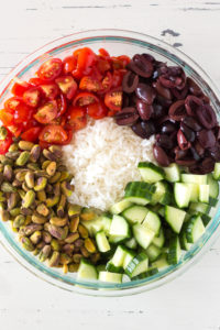 ingredients for greek rice salad in a bowl