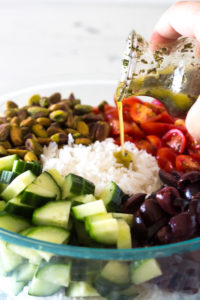 pouring dressing over greek rice salad