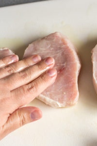rubbing oil on pork chops