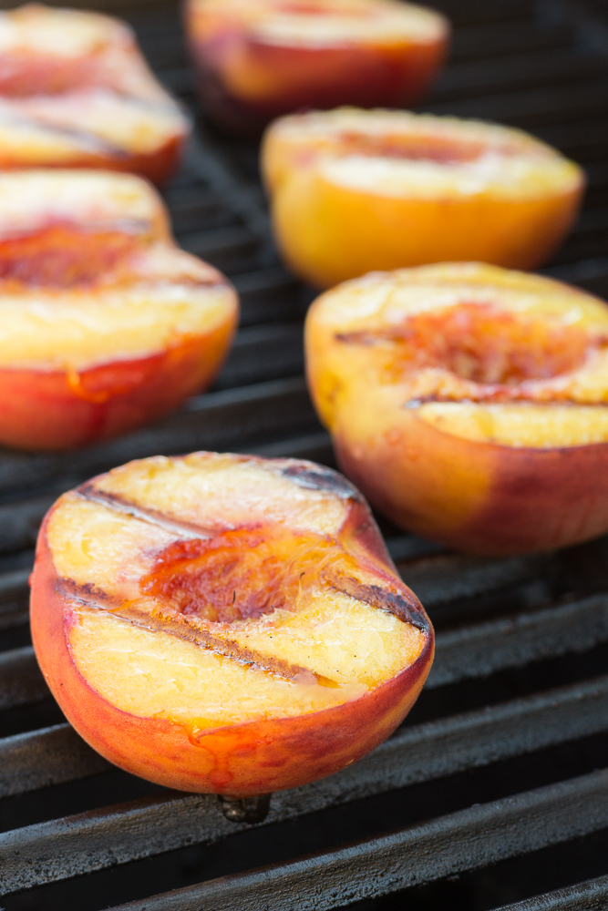 grilled peach halves on a grill