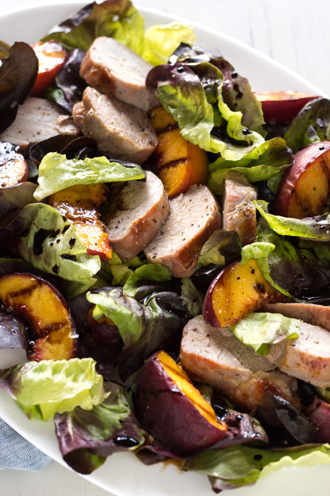 grilled pork and peach salad on a white platter