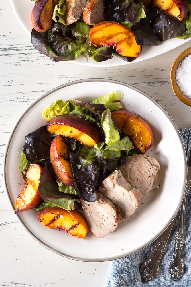 a white plate with grilled pork and peach salad