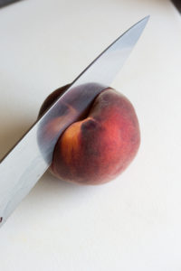 a knife cutting a peach in half