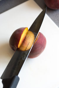 separating two peach halves with a large knife