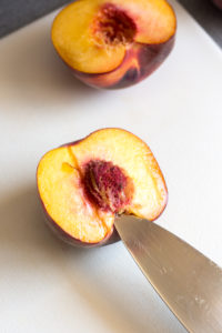 getting a peach pit out with a knife