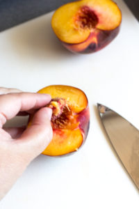 fingers removing a peach pit from half a peach