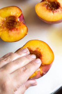 rubbing oil into a peach half
