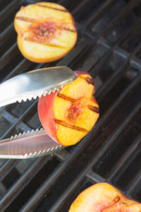 flipping a grilled peach half with tongs