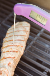 a meat thermometer checking grilled pork