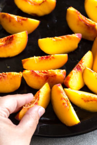 rubbing oil on sliced peaches