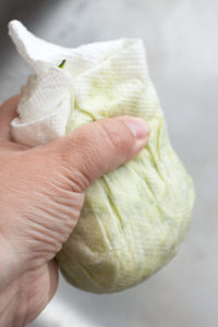 squeezing water out of grated zucchini with paper towels