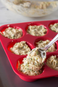 scooping zucchini muffin batter into a silicone muffin tin