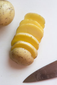 slices of yukon gold potatoes on a cutting board