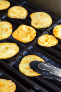 setting sliced potatoes onto a grill with tongs
