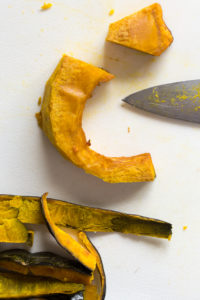 a slice of kabocha squash, peeled on a cutting board