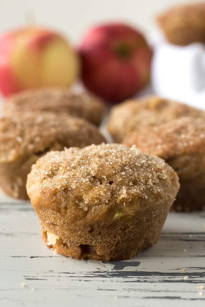 apple cinnamon muffins on a table with apples in the background