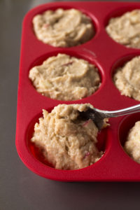 scooping muffin batter into a red silicone muffin tin with a spoon
