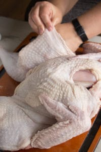 separating the skin from the thigh of a raw turkey with a hand.