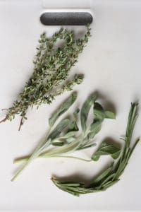 fresh sage, rosemary, and thyme on a white cutting board