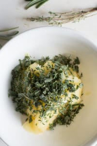 chopped fresh herbs on top of softened ghee in a white bowl